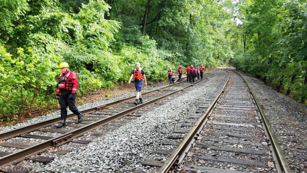 Crews walking the railroad bed to the day care
